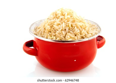 Red pan with healthy brown rice isolated over white