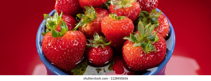 Red panoramic photograph of fresh strawberries in a blue bowl.