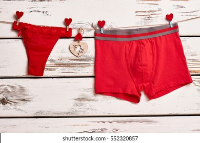 Red panties and boxer briefs. Underwear on rope with clothespins. Red color as love symbol.