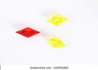 Red paper boat among other white. Leadership, white crow, individuality. Piranhas and a shark. Not like everyone else. Origami. Top view, flat lay, copy space.