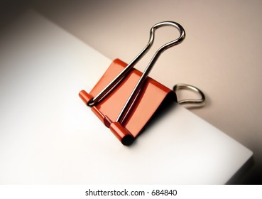 Red paper clip binding a stack of documents.