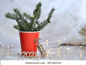Red paper Coffee cup complete spruce branch withnumbers 2021, sleigh, garland, Snowflakes. Holiday concept for a coffee Shop. Xmas composition.  New Year and Christmas concept.