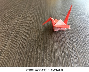 Red paper crane on wooden plate