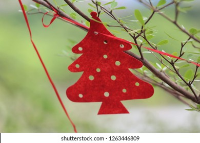 A red paper cut out Christmas tree decorating a real tree