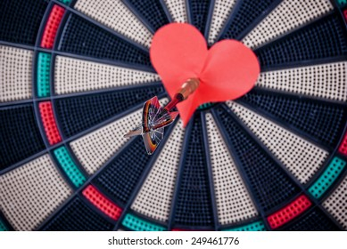 Red paper heart in the center of darts target, dart arrow, concept