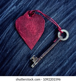 Red paper heart and an old key on a black grunge effect background.