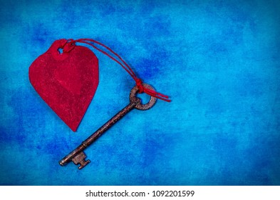 Red Paper Heart & and Old Key with copy space on a grunge effect blue background.