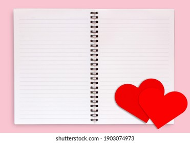 Red paper heart on blank open book isolated on pink background top view with copyspace. Love and valentines day concept