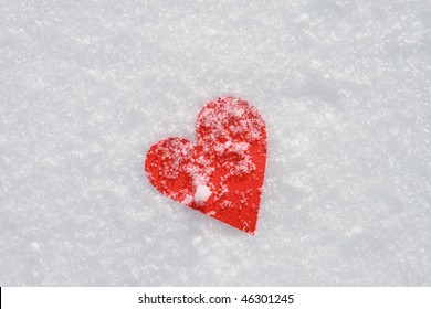 Red paper heart in the snow.