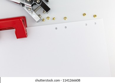 Red paper hole puncher isolated on white background.