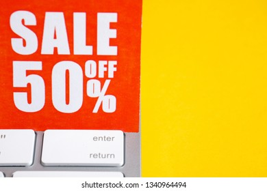 """Red paper label with an inscription """"sale off 50%"""" on a white keyboard on a yellow background. Copy space."""