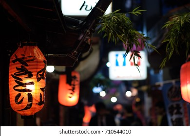 "Red paper lanterns advertising chicken skewers in a dark alley in Tokyo at night. The sign reads ""Yakitori"" in Japanese."