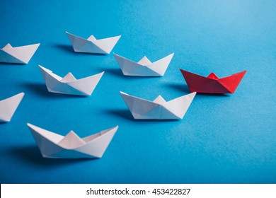 Red paper leader ship with fleet. Concept for leadership, management, motivation, difference and uniqueness.