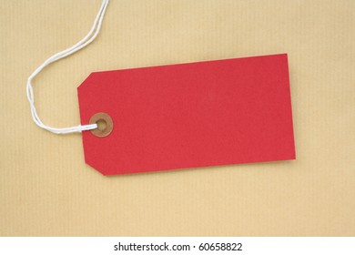 Red paper luggage tag or label with copy space on a brown wrapping paper background