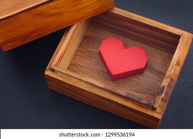 Red paper origami heart inside wooden box. Close up.