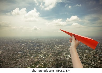 Red paper plane in young women hand with cityscape background,Copy space, Business concept.