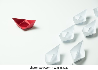 Red paper ship changing direction and white ones. New idea, change, trend, courage, creative solution, innovation and unique way concept.