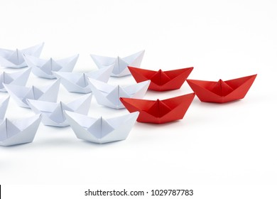 Red paper ship leader among white ships. Business and leadership concept. Isolated on white background. Paper craft and origami.