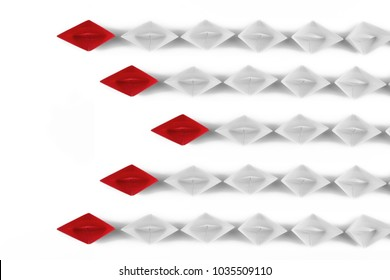 Red paper ship leader among white ships. Business and leadership concept. Isolated on white background. Paper craft and origami. Close up and top view.