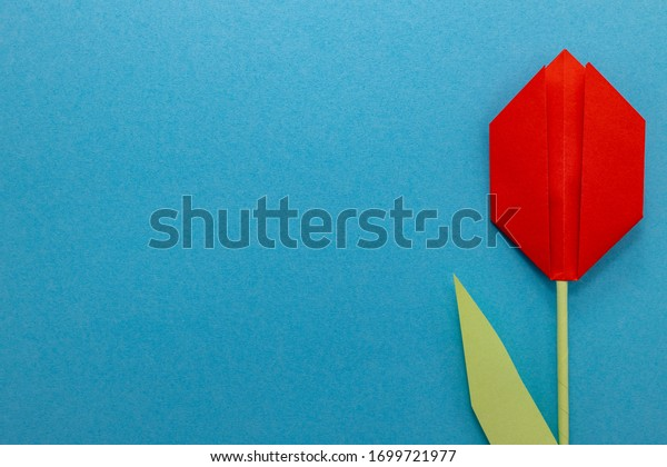 Red paper tulip on a blue background. Top view with room for copy.