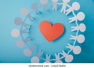 Red paper Valentines Day heart against a blue background