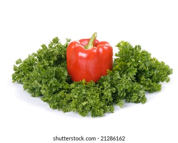 red paprika in green parsley isolated on white background