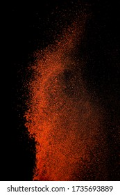 Red paprika spices powder explosion, flying chili pepper isolated on black background. Splash of spice background.