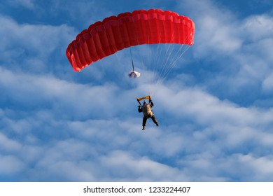 Red parachute is in the amazing blue sky. Military parachutist is landing with big bag,