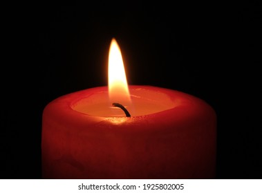 Red paraffin mournful commemorative thick candle burns on a black background close-up