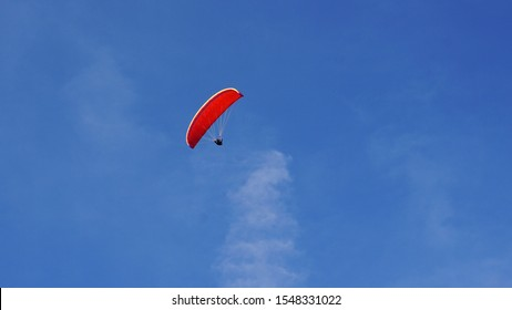 Red paraglide contrast agains bright blue sky and white cloud