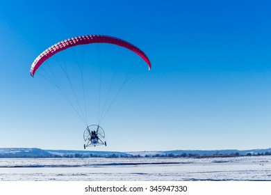Red paraglide flying over clear blue winter sky