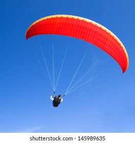 red paraglider on the blue sky