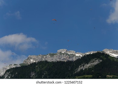 Red paraglider and paragliders flying high above La Tournette above Lake Annecy  France