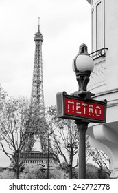 Red Paris metro subway entry sign with Eiffel tower in the background, Paris, France