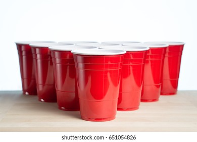 Red party cups on wooden table for beer pong tournament isolated on white. College alcohol containers with free empty blank copy space for text. Event marketing and promotion background template.