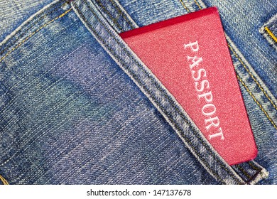 Red passport in blue jeans back pocket