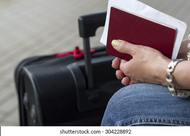 Red passport in female hands next to luggage, outdoor cropped shot, concept of travel