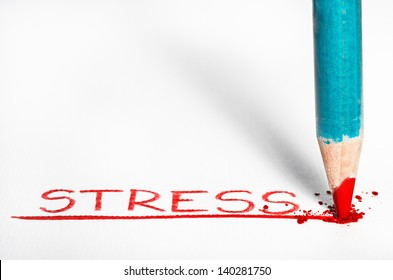 A red pastel pencil writing the word Stressed out.