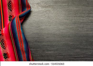 Red pattern tablecloth on wooden table for background. Fabric texture. Wooden texture