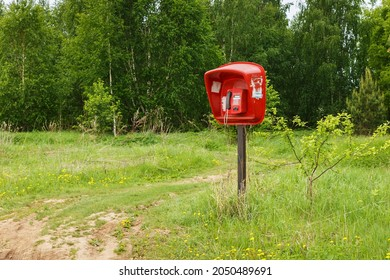 red payphone. Payphone standing in the field. Village telephone. Russia