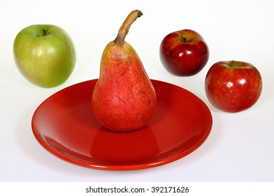 Red pear on the red plate with green and red apples isolated on white