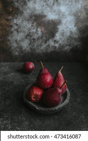Red pears in a bowl on a rustic background