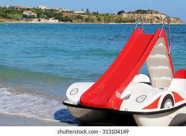 Red pedalo boat with slide on the beach