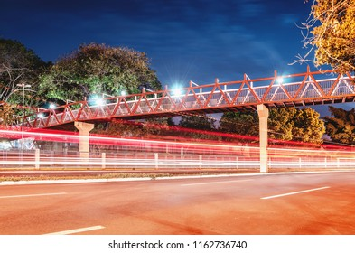 Red pedestrian bridge above the street. Light trails from the cars passing on the street. Red bridge at night of the Horto Florestal in Campo Grande MS, Brazil.