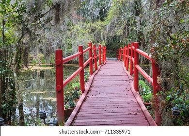 Red pedestrian bridge in an outdoor garden in the lowcountry of Charleston, South Carolina.
