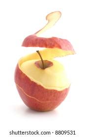 red peeled apple. peel levitates showing pulp