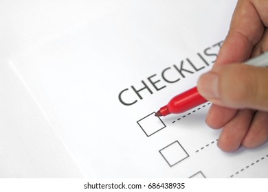 Red pen with blank checklist.