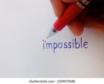 Red pen using to write apostrophe mark to change impossible word to I'm possible, inspiration quote for changing negative mind. White background concept wording.