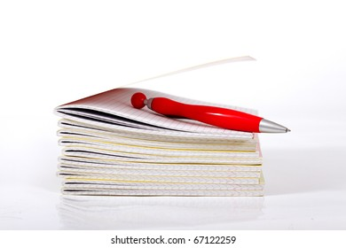 Red pen and workbooks.