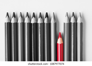 Red pencil among black and white on light background.